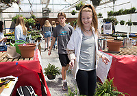 NWA Democrat-Gazette/CHARLIE KAIJO Skylurr Patrick, 17, (from left) and Bryan Kendall, 17, (center) carry plants for a customer, Thursday, April 12, 2018 at the Rogers High School greenhouse in Rogers.<br />