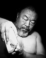 Chinese artist Ai Weiwei poses for a portrait while shooting the photographer with his phone. July 6th, 2015. Beijing, China.