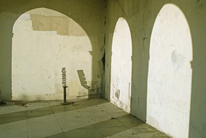 The remains of a wooden bench in a shelter on Dukes Mound  near Brighton Marina, England. The wall shows signs of graffiti having been covered up.
