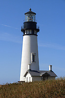 The 93-foot white tower stands 162 feet above sea level isolated on a narrow point of land jutting into the Pacific Ocean hightlighted by a bright blue sky. This brick structure was lit for the first tiem in 1873 and is part of the Yaquina Head Outstanding Natural Area.