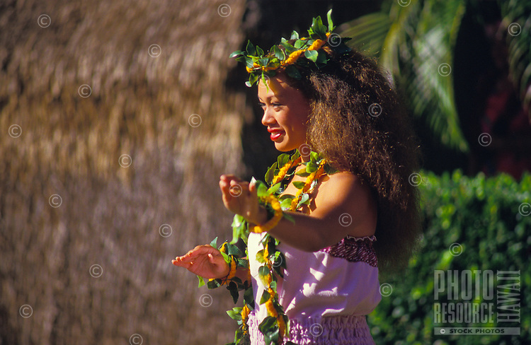 Woman wearing leis dancing hula in front of a grass hut