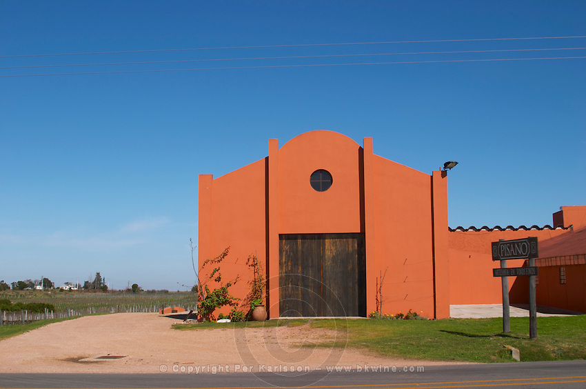 A view over the main winery building and a sign to the winery. Painted in ochre red and with a grass lawn in front. Bodega Pisano Winery, Progreso, Uruguay, South America