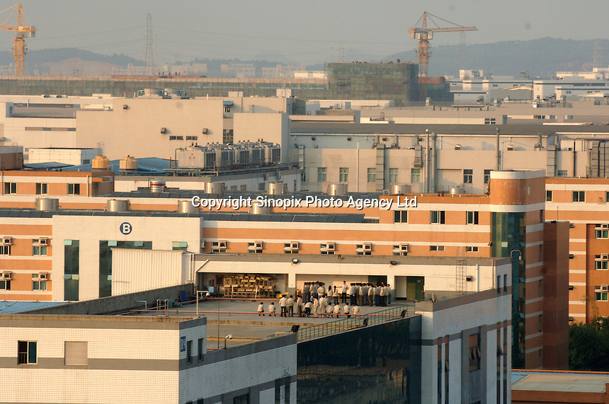 Workers are drilled on the roof at Taiwanese owned Foxconn plant, a high end electronic manufacture that employs well over 140,000 workers at their plant at Longhua, Shenzhen, China that consists of more than 10 large factories and 11 research units at a sprawling complex that covers several square kilometers. According to senior engineers Foxconn produce over 40% for apple at this plant including the i.pod Nano, G5 computer and Macmini computer. Payment for labour before overtime is around 800 RMB (56 pounds sterling). Foxconn employ almost a million workers in China..02 Mar 2006