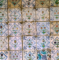 A detail of antique blue and white tiles with floral motifs which line the fireplace in the entrance hall