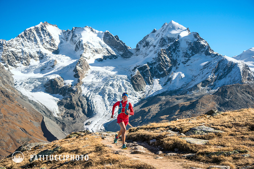 Trail running above the Rosegtal with Piz Bernina and Piz Roseg in the background. Pontresina, Switzerland