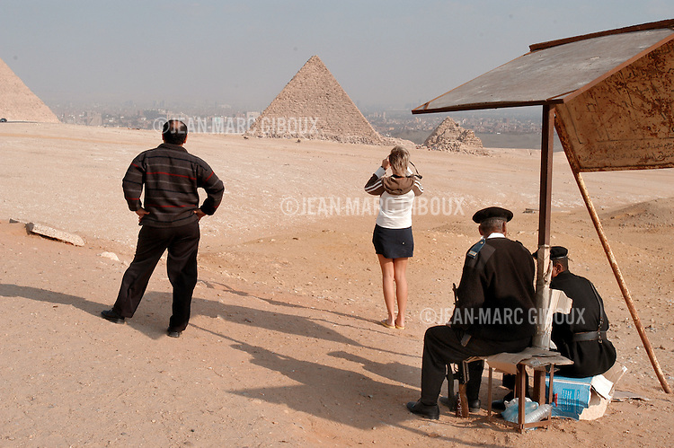 CAIRO - NOVEMBER 30, 2004 : Police security is present as foreign and egyptian tourists visit the 5000 years old Giza pyramids in Cairo, on November 30, 2004. Sitauated high on a desert plateau overlooking sprawling Cairo, Giza is the most visited tourist site in Egypt ,with the Sphinx and the 481ft high great Pyramid. Tourism has been on the decline in Egypt following a series of terrorist attacks targeting foreign tourists. (Photo by Jean-Marc Giboux)