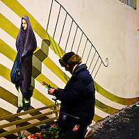 After the Islamic Revolution of 1979, revolutionary mural paintings proliferated across Tehran. Now comparable with the mexican revolutionary mural movement of the 1920s and 1930s, the murals institutionalize the ideas and ideals of the iranian revolution, and are present in everyday life, such as close to his informal flower seller operating in Northern Tehran.<br /> <br /> More on this subject: http://www.pbs.org/wgbh/pages/frontline/tehranbureau/2012/06/art-painted-politics-the-mural-in-modern-iran.html