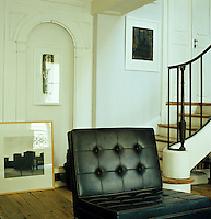 A black leather chair by Florence Knoll in the library which is located at the foot of the grand staircase