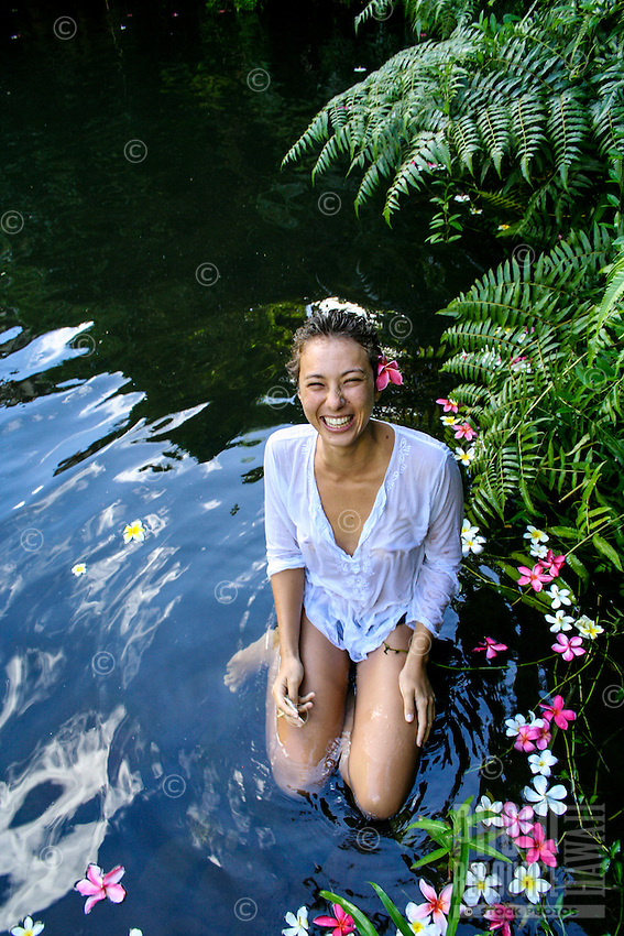 A woman in a white coverup laughs in a pond with floating plumeria flowers, Kane'ohe, O'ahu.