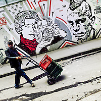 A Colombian street vendor passes in front of a graffiti stencil artwork, created by an artist named Toxicómano Callejero, in the center of Bogotá, Colombia, 13 March, 2016. A social environment full of violence and inequality (making the street art an authentic form of expression), with a surprisingly liberal approach to the street art from Bogotá authorities, have given a rise to one of the most exciting and unique urban art scenes in the world. While it's technically not illegal to scrawl on Bogotá's walls, artists may take their time and paint in broad daylight, covering the walls of Bogotá not only in territory tags and primitive scrawls but in large, elaborate artworks with strong artistic style and concept. Bogotá has become an open-air gallery of contemporary street art.