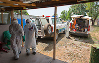 Health care workers help new patients enter the ETU from ambulances at ELWA II in Monrovia, Liberia on Monday, March 9, 2015. Ben Smith, hygienist supervisor, (at left, facing) can be seen wearing his portrait on his PPE.<br /> Occidental College professor Mary Beth Heffernan's PPE Portrait Project involves creating wearable portraits of the health care workers who must wear PPE (personal protective equipment) when working with patients.<br /> (Photo by Marc Campos, Occidental College Photographer) Mary Beth Heffernan, professor of art and art history at Occidental College, works in Monrovia the capital of Liberia, Africa in 2015. Professor Heffernan was there to work on her PPE (personal protective equipment) Portrait Project, which helps health care workers and patients fighting the Ebola virus disease in West Africa.<br />