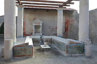 Garden area with benches in a summer triclinium beneath a pergola supported by 4 stucco columns, inner walls with Nilotic landscape scenes and a central fountain with bronze statuette, in the Casa dell Efebo, or House of the Ephebus, Pompeii, Italy. This is a large, sumptuously decorated house probably owned by a rich family, and named after the statue of the Ephebus found here. Pompeii is a Roman town which was destroyed and buried under 4-6 m of volcanic ash in the eruption of Mount Vesuvius in 79 AD. Buildings and artefacts were preserved in the ash and have been excavated and restored. Pompeii is listed as a UNESCO World Heritage Site. Picture by Manuel Cohen