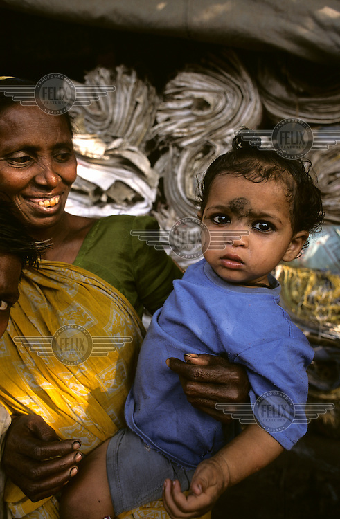 A mother and child stand in front of a recycling plant in a slum area of Kolkata.
