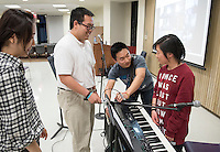 From left, Laura Yoon '18 looks on as Nick Yeh '17 checks in with musicians Justin Choi '17 and Eileen Lee '16 before leading the InterVarsity Large Group meeting on Maundy Thursday of Holy Week. The meeting, in Lower Herrick, was well-attended and culminated with the Washing of Feet ceremony. March 24, 2016.<br />