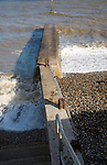 Waves breaking on differing beach levels either side of a concrete groyne, Dovercourt, Harwich, Essex, England