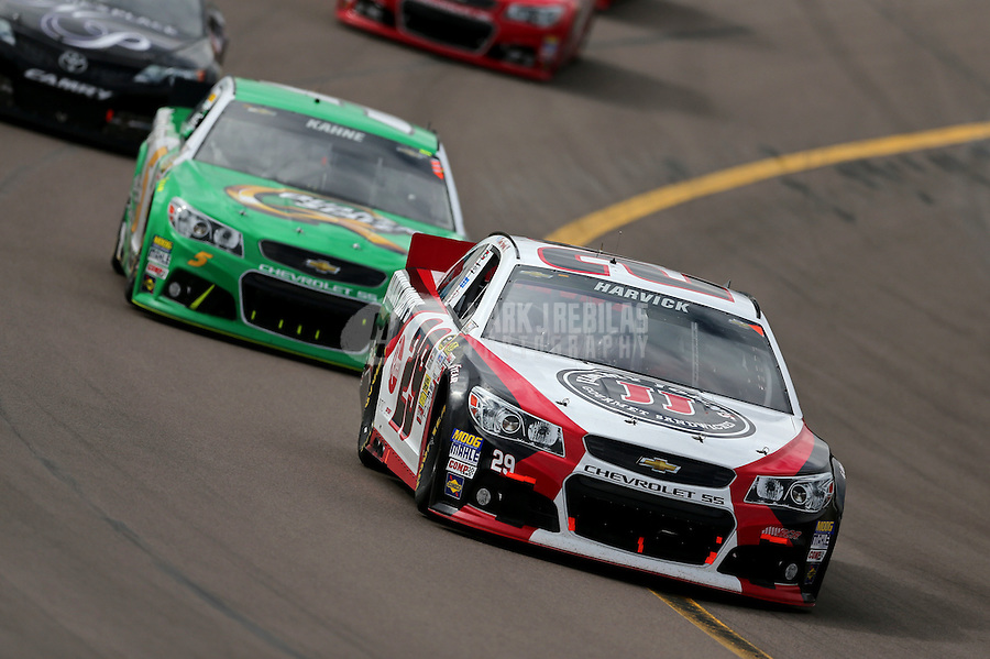 Mar. 3, 2013; Avondale, AZ, USA; NASCAR Sprint Cup Series driver Kevin Harvick leads Kasey Kahne during the Subway Fresh Fit 500 at Phoenix International Raceway. Mandatory Credit: Mark J. Rebilas-