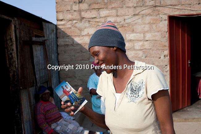 GA-MASEHLONG, SOUTH AFRICA - AUGUST 7: Elisa Morolong, age 19, and a close friend of Caster Semenya looks at a photo of both of them outside her house in GA-MASEHLONG, South Africa.Caster Semenya won the 800 meters world championship gold medal in Berlin in 2009 was recently cleared to run after her career was held back due to gender testing. She grew up in this rural village in Limpopo, northern South Africa, and she started running only a few years ago, and quickly appeared from nowhere to the world stage. After being banned for almost a year she was cleared by the IAAF and cleared to compete in July 2010. (Photo by Per-Anders Pettersson/Getty Images)
