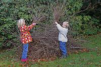 Igelschutz, Igel - Schutz, Kinder bauen im Herbst ein Igelquartier zum Überwintern aus Reisig im Garten, Reisighaufen, Asthaufen, Naturgarten
