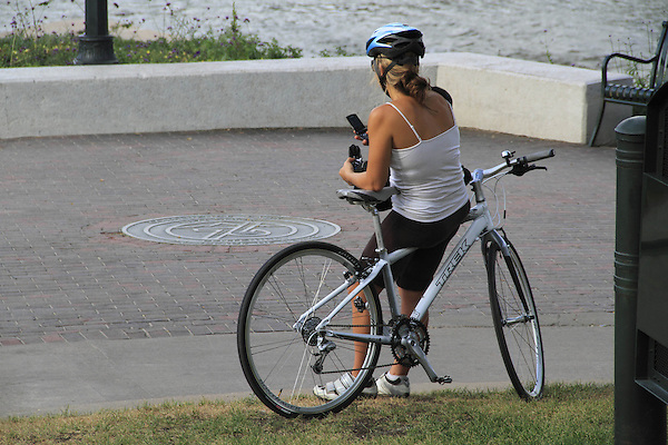 Woman biker using her smart phone at Confluence Park, Denver, Colorado. .  John offers private photo tours in Denver, Boulder and throughout Colorado. Year-round.