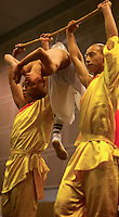 Monks from the Shaolin temple, Henan, China, performing martial arts feats. A young monk controls his abdominal muscles and sucks in his stomach to create a vaccum that fixes the bowl on to his stomach. Two other monks then lift him up using only the vaccum pressure.