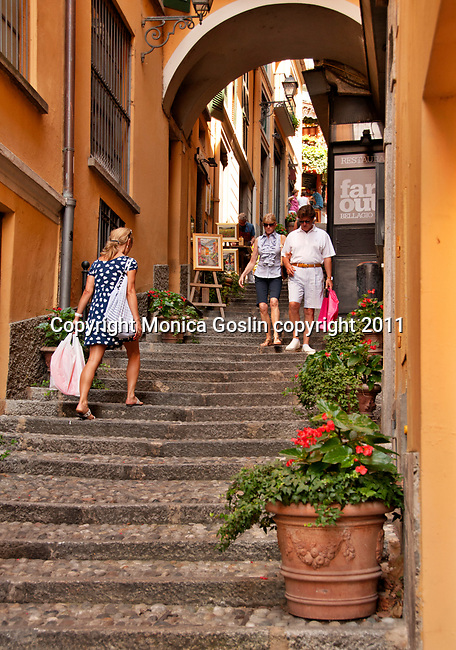 Tourists walk down a shopping street in the resort town of Bellagio on Lake Como, Italy in the summer