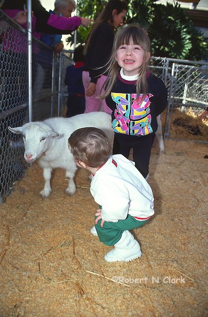 Boy and girl with baby goat at county fair