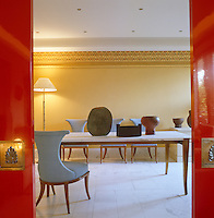 Red-lacquered sliding doors divide the dining room from the living room and the marble-topped table displays a collection of ceramic pots by sculptor Paul Philip