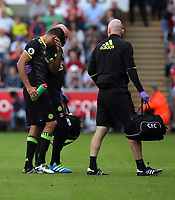 Diego Costa of Chelsea (L) is moved off the pitch by physiotherapists during the Premier League match between Swansea City and Chelsea at The Liberty Stadium on September 11, 2016 in Swansea, Wales.