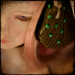 Close up of a dolls face with green beads in her hair