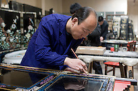 Marquetry craftsman at work on lacquer fire screen at souvenir and furniture factory, Xian, China