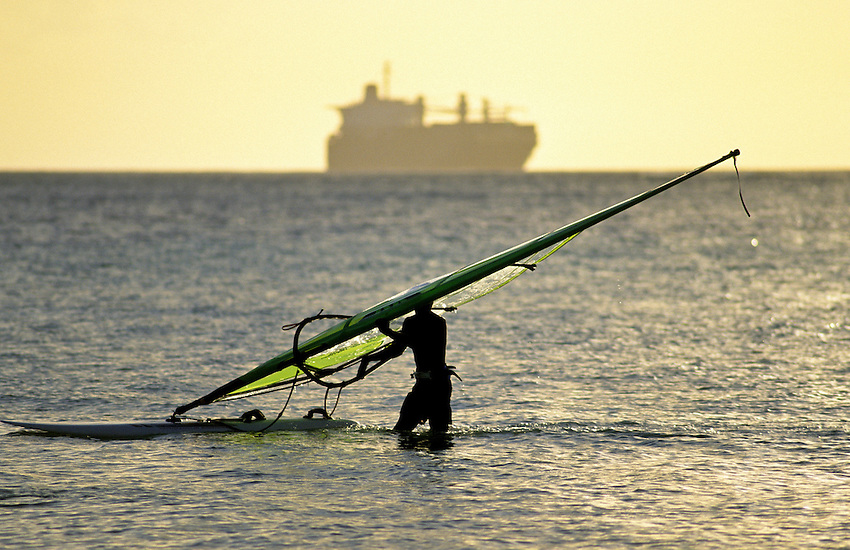 A WINDSURFER IS FINISHING THE DAY AS A LARGE CONTAINER SHIP PASSES ON THE HORIZON, SAIPAN, PACIFIC NEAR GUAM