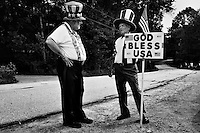 "Men dressed as Uncle Sam carrying a sign that reads ""God Bless USA"" talk before the start of the 4th of July parade in Amherst, New Hampshire. Republican presidential candidates Mitt Romney and Jon Huntsman walked in the parade as part of their campaign for the 2012 presidential election."