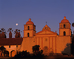 Santa Barbara Mission at sunrise with moonsetting with warm light on facade, Santa Barbara, California USA