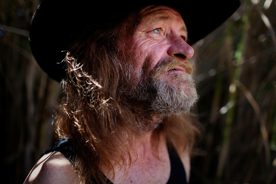 """Ventura, California, July 23, 2010 - A portrait of Tim 'Timbow' Bowman at his campsite along Ventura River bottom. Bowman has been homeless and living along the river since the early 1990's. In 1987 Bowman's 18-month-old daughter, Miranda Laurel, died from Lyme disease. His wife left him soon afterwards. A year later he fell through a plate glass window while working on a construction site, leaving him disabled and unable to work construction. He says the loss of his wife and daughter and his struggles with work sent him into a spiral. He eventually lost his home. He says he lives in the 300+ community along the river bottom because he """"feels at home."""" Adding, """"I feel loved down here. Up there is nothing but trouble."""" The two-mile stretch of river bottom from the Pacific to Stanley Road is home to about 300 homeless, who have carved tunnels and paths into the tall grass and bamboo. Bowman, who survives off of SSI, says, """"I lead an honest life. I don't steal, I don't rob and I share whatever I can."""" ."""