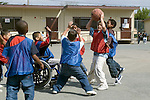 Oakland CA Elementary school students, including one disabled boy in wheel chair, playing casual game of basketball at recess  MR