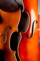 "The ""C"" bouts and f holes of two classical violins or fiddles on a grey background."