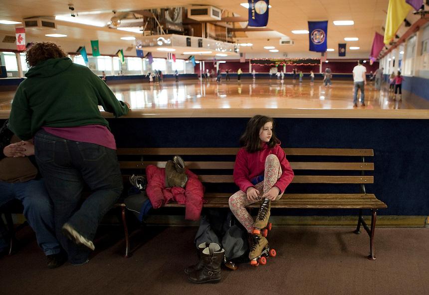A girl lances up her rented roller skates at the oak Park Roller Shaking rink in Portland.