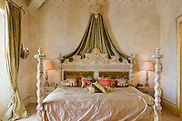 An imposing carved bed is graced with a green silk bed hanging held by a wall-mounted corona