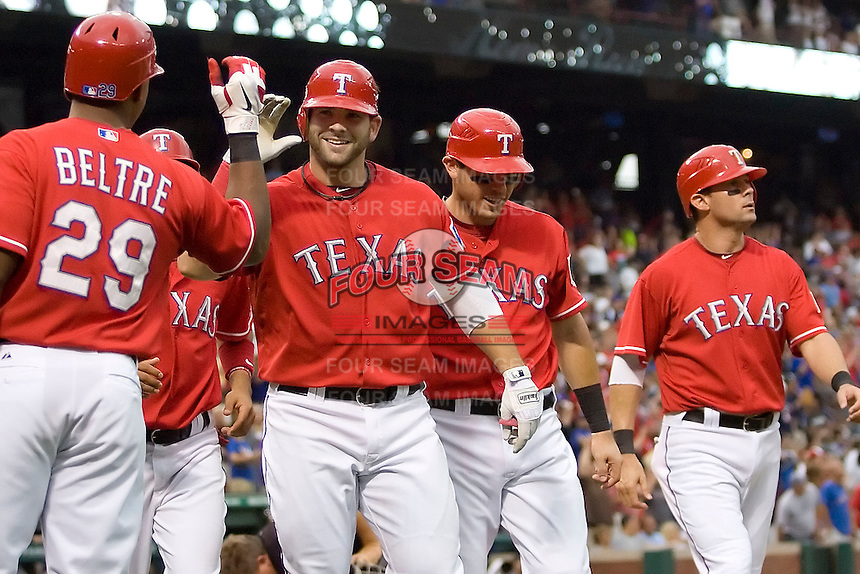 Texas Rangers first baseman Mitch Moreland (18) is greeted at home after hitting a grand slam home run against the Oakland Athetics in American League baseball on May 11, 2011 at the Rangers Ballpark in  Arlington, Texas. (Photo by Andrew Woolley / Four Seam Images)