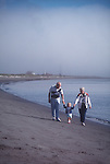 Beach, Grandparents walking grandchild, Fort Worden, Point Wilson, Port Townsend, Puget Sound, Washington State, U.S.A. Washington State Parks,