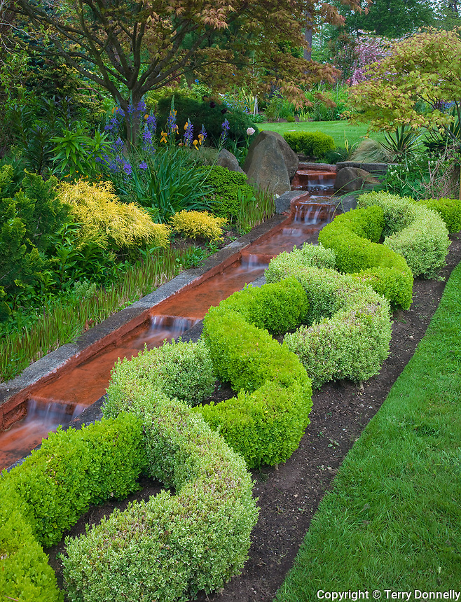 Vashon Island, Washington<br /> Garden viewe of a boxwood knot garden and terraced waterfall