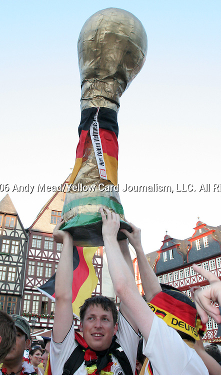 30 June 2006: A fan holds a giant Jules Rimet trophy in the are as Germany fans celebrate in the town square in Frankfurt, site of several games during the FIFA 2006 World Cup. Germany had just defeated Argentina in a Quarterfinal game played in Berlin.