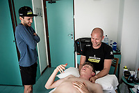 physiotherapist Dan Guillemette working on Mitchelton-Scott rider Lucas Hamilton (AUS) in the team hotel during restday 1 (20 may) of the 102nd Giro d'Italia 2019, while Simon Yates (GBR/Mitchelton-Scott) stops by for a chat<br /> <br /> ©kramon