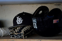 Long Island Blackbirds hat, glove and batting helmet in the dugout during a game against the Illinois State Redbirds at Chain of Lakes Stadium on March 8, 2013 in Winter Haven, Florida.  Illinois State defeated Long Island 6-4.  (Mike Janes/Four Seam Images)