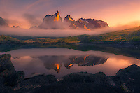 Los Cuernos del Paine peeks through low clouds and fog, illuminated by the rising sun.  Just moments later, a heavy fog came through as the scene vanished into the light of day.<br />