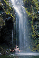 Woman enjoys a waterfall on the road to Hana, Maui, Hawaii, USA.