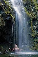 Woman enjoys a waterfall on the road to Hana, Maui, Hawaii, USA.