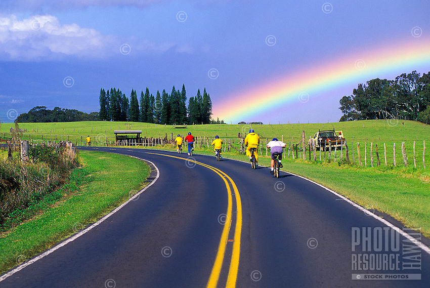 Downhill biking on Haleakala road with rainbow