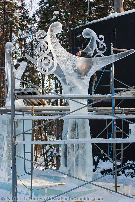 """Ice sculptor from Russia adds detail to a multi block sculpture titled """"The Tree Graces"""" for the 2009 World Ice Art Championships in Fairbanks, Alaska. Team members: Sergey Tselebrovsky, Russia; Dimitry Gorokhov, Russia; Sergey Zaplatin, Russia; Andy GertlerNY, USA"""