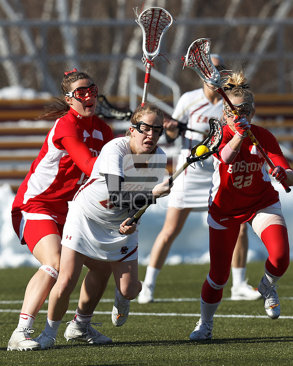 Boston College midfielder Sarah Mannelly (6) drives forward as Boston University midfielder Ally Adams (15) and Boston University defender Monica Baumgartner (22) defend..Boston College (white) defeated Boston University (red), 12-9, on the Newton Campus Lacrosse Field at Boston College, on March 20, 2013.